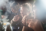 Michelle Blade (l-r), Anouk Vlug, and Nate Stevens enjoy hot tea and breakfast in a backcountry cabin in Foxdalen, Svalbard.