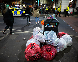 © Licensed to London News Pictures. 12/04/2021. Manchester, UK. Rubbish placed in bags by a bin in the Stevenson Square . People on a night out in Manchester City Centre as government restrictions to control the spread of Coronavirus are eased across the UK. Pubs, restaurants, hairdressers, gyms and non essential retailers are now permitted to serve customers within restrictions. Photo credit: Joel Goodman/LNP