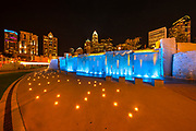 Many of the skyscrapers in downtown Charlotte, North Carolina, are visible at night over the colorful, lighted water feature called Childhood Muse in Romare Bearden Park.