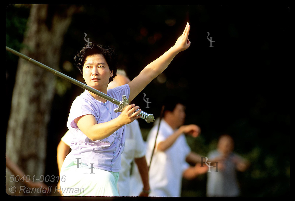 Woman practices sword play at sunrise in Jin An Park in central Shanghai. China