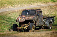 A beat up old pick-up, with no engine, covered with moss & lichen.