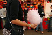 adult female person walking with cotton candy at a fairground