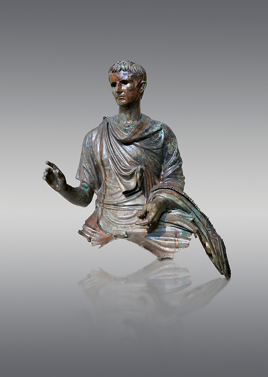 Roman bronze statue fragment of emperor Augustus, Circa 12-10 BC,  found in the Agean sea of  the Island of Euboea, Athens National Archaeological Museum. cat no X 23322. Against grey.<br /> <br /> The emperor Augustus is depicted in mature age mounting a horse. He wears a tunica with verivle purple stripes (clavus purpurea) fringed with a meander pattern. Icongraphic features of bthe Prima Porta and Actuim type of statue are incorporated in this brnze statue. The right hand is raised in a gesture of offical greeting and the left hand held the horses reigns. A ring on the finger gears has engraved the symbol of Pontifles Maximus assumed by Augustus in 12 BC .<br /> <br /> If you prefer to buy from our ALAMY STOCK LIBRARY page at https://www.alamy.com/portfolio/paul-williams-funkystock/greco-roman-sculptures.html . Type -    Athens    - into LOWER SEARCH WITHIN GALLERY box - Refine search by adding a subject, place, background colour, etc.<br /> <br /> Visit our ROMAN WORLD PHOTO COLLECTIONS for more photos to download or buy as wall art prints https://funkystock.photoshelter.com/gallery-collection/The-Romans-Art-Artefacts-Antiquities-Historic-Sites-Pictures-Images/C0000r2uLJJo9_s0
