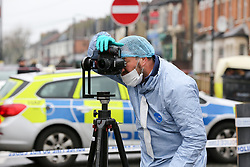 © Licensed to London News Pictures. 09/04/2019. London, UK. A forensic officer takes photographs within the crime scene on Church Road, Manor Park, East London where a man in his 20s was shot and stabbed to death on Monday 8 April 2019. Police were called around 9.30pm and the man was was found with knife and gunshot wounds. The victim was pronounced dead at the scene. Photo credit: Dinendra Haria/LNP