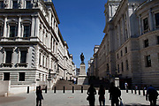 Tourists walk towards the Foreign Office (left) and H.M. Teasury in St James' in central London.