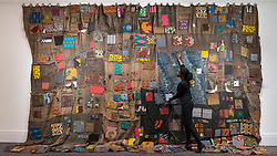 "© Licensed to London News Pictures. 23/03/2018. LONDON, UK. A staff member views ""Chale Wote"", 2014, by Ibrahim Mahama (Est. GBP60,000-90,000).  Preview of Modern and Contemporary African Art sale at Sotheby's, New Bond Street.  The auction will take place on 28 March 2018.   Photo credit: Stephen Chung/LNP"