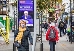 © Licensed to London News Pictures. 02/11/2020. London, UK. Shoppers go out wearing masks in Richmond Town centre in South West London two days before lockdown with a digital display showing Boris Johnson announcing new lockdown measures. Prime Minister Boris Johnson announced on Saturday new Covid lockdown restrictions for England from Thursday with pubs, restaurants, non-essential shops and gyms to close. Today, the Prime Minister will give a statement to the commons as he warns MPs that deaths from Covid-19's second wave could be twice as high as the first ahead of MPs voting on the Government's 4 week lockdown measures. Photo credit: Alex Lentati/LNP