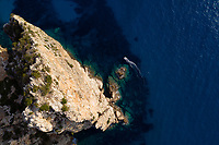 Aerial view above of touristic boat sailing along Sardinia cliffs, Italy.