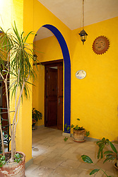 North America, Mexico, Guanajuato State, Guanajuato, yellow arch in hotel courtyard wtih plants and Mexican art.  The historic city of Guanajuato is a UNESCO World Heritage Site.  PR