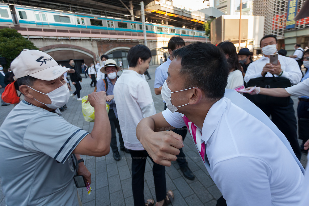 Former actor, Taro Yamamoto, leader of the anti-establishment political party Reiwa Shinsengumi, ,touches elbows with supporters while electioneering in Shimbashi for the 2020 Tokyo Gubernatorial elections. Tokyo, Japan. Thursday July 2nd 2020. The  elections for Tokyo Governor take place on Sunday July 5th. The incumbent, Yuriko Koike (not pictured) is expected to easily win reelection for her second term as leader of Japan's capital city. Photo by Damon Coulter/AFLO