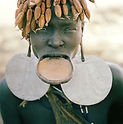 Mursi tribal woman with plate in lip and beads in hair, Omo Valley, Southern Ethiopia. The Mursi consider the lip plate as a form of beauty.