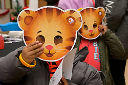 Kids hold up Daniel Tiger Masks at the WHYY table during the winter fest celebration at the Free Library branch in Olney, on December 16, 2018. (Bastiaan Slabbers for WHYY)