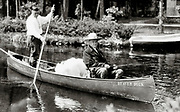 "President Calvin Coolidge (right) fishes the Brule River in Douglas County, Wisconsin, with Native American guide John LaRock in 1928. The canoe is named ""Beaver Dick"" and in the middle is Coolidge's white collie, Rob Roy."