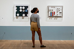 """© Licensed to London News Pictures. 13/07/2021. LONDON, UK. A staff member poses with two works called """"Relief"""", 1936.   Preview of the first UK retrospective exhibition at Tate Modern of works by Sophie Taeuber-Arp (1889-1943), one of the foremost abstract artists and designers of the 1920s and 30s. Works from Taeuber-Arp's accomplished career as a painter, architect, teacher, writer, and designer of textiles, marionettes and interiors is on 15 July – 17 October 2021.   Photo credit: Stephen Chung/LNP"""