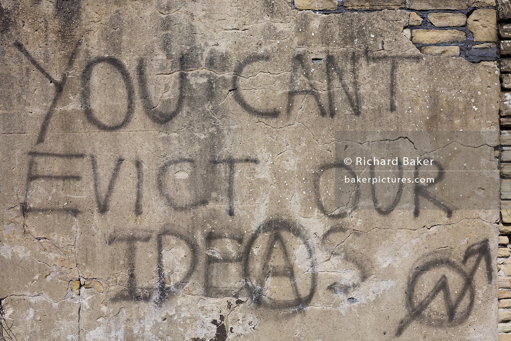 Graffiti sprayed on a rendered brick wall proclaims that a higher authority 'Can't evict our ideas'. This message of resistance by the underdogs of a moral majority appears on a part of wasteland in the Yorkshire city of Bradford, where the residents of an estate near the city centre have been forcibly removed to make space for a new development. Before their migration, the anonymous, downtrodden people were desperate enough to write this piece of anarchical philosophy that might be seen as a metaphor for a class war against the establishment by The People; the working classes otherwise known in Marxist ideology, as the Proletariat - a kind of thought from the (Orwellian) novel Nineteen Eighty-Four, by George Orwell.
