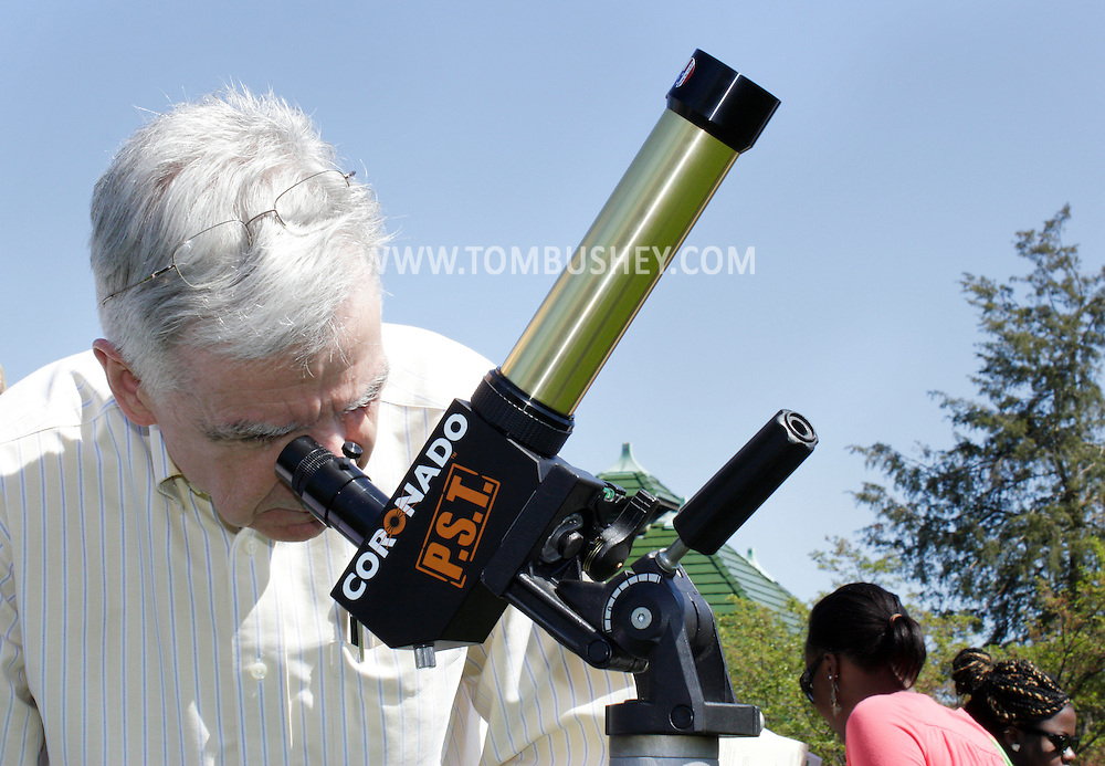 Middletown, New York - A man looks at the sun through a Coronado Personal Solar Telescope during an Earth Day celebration on the green at SUNY Orange on April 19, 2012.