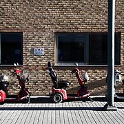 Early morning, electric wheelies parked up. Lundtoftegade is a housing estate in the heart of Copenhagen. The estate has been on the controversial Ghetto List for years but wastaken off 1st of December 2020. The Ghetto List is based on the Ghetto Law introduced by the Danish Govenrment in 2018. In 2020 a huge campaign was launched to raise 50.000 signatures demanding the Danish Parliament to reconsider the law and to abolish it. Part of the campaign was the national portrait poster campaign 'We ARE the mixed city'. More than 100 local residents in joined the campaign and were photographed in a small make shift studio set up in Lundtoftegade. These images are fragments of life in and around Lundtoftegade 2020.