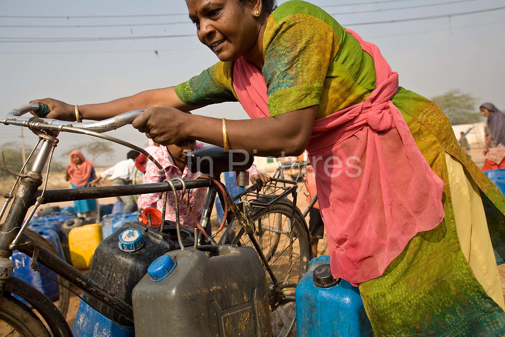 A woman pushes her bike home after filling many cans from a water tanker in Kusumpur Pahari. The slum, built more than thirty years ago has no running water or sewage facilities. The only water supply come from the Municipal  JAL Board water trucks that visit several times a day. The deliveries are supposed to be free but in reality, residents must pay bribes to have the water delivered.