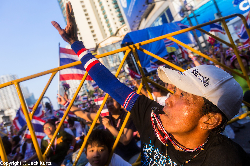 """13 JANUARY 2014 - BANGKOK, THAILAND: A Thai man waves to a TV news helicopter during an anti-government protest in Bangkok. Tens of thousands of Thai anti-government protestors took to the streets of Bangkok Monday to shut down the Thai capitol. The protest was called """"Shutdown Bangkok"""" and is expected to last at least a week. The Shutdown Bangkok protest is a continuation of protests that started in early November. There have been shootings almost every night at different protests sites around Bangkok, including two Sunday night, but the protests Monday were peaceful. The malls in Bangkok stayed open Monday but many other businesses closed for the day and mass transit was swamped with both protestors and people who had to use mass transit because the roads were blocked.    PHOTO BY JACK KURTZ"""