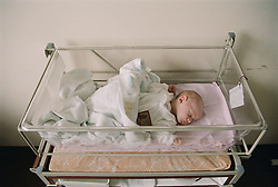 New born baby lying in cot on Maternity Unit in hospital,