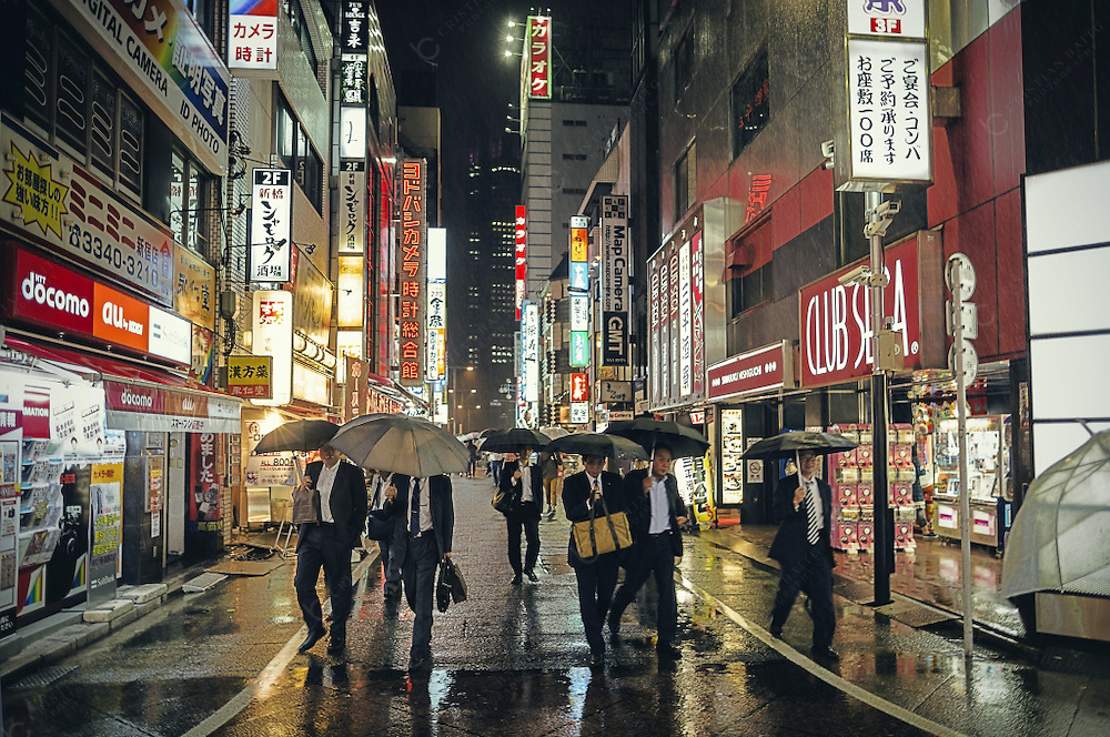 People walking in Shinjuku at night in Tokyo. Shinjuku is one of the 23 special wards of the city. It is one of the major business and administrative parts of the capital. The government of the city is located here as well as many big world corporations that have their offices in this area. It has an extension of 18 square kilometers and a population of more than 300000 thousand people living here and many more comming to work everyday. It is also known for having the busiest train station in the world.