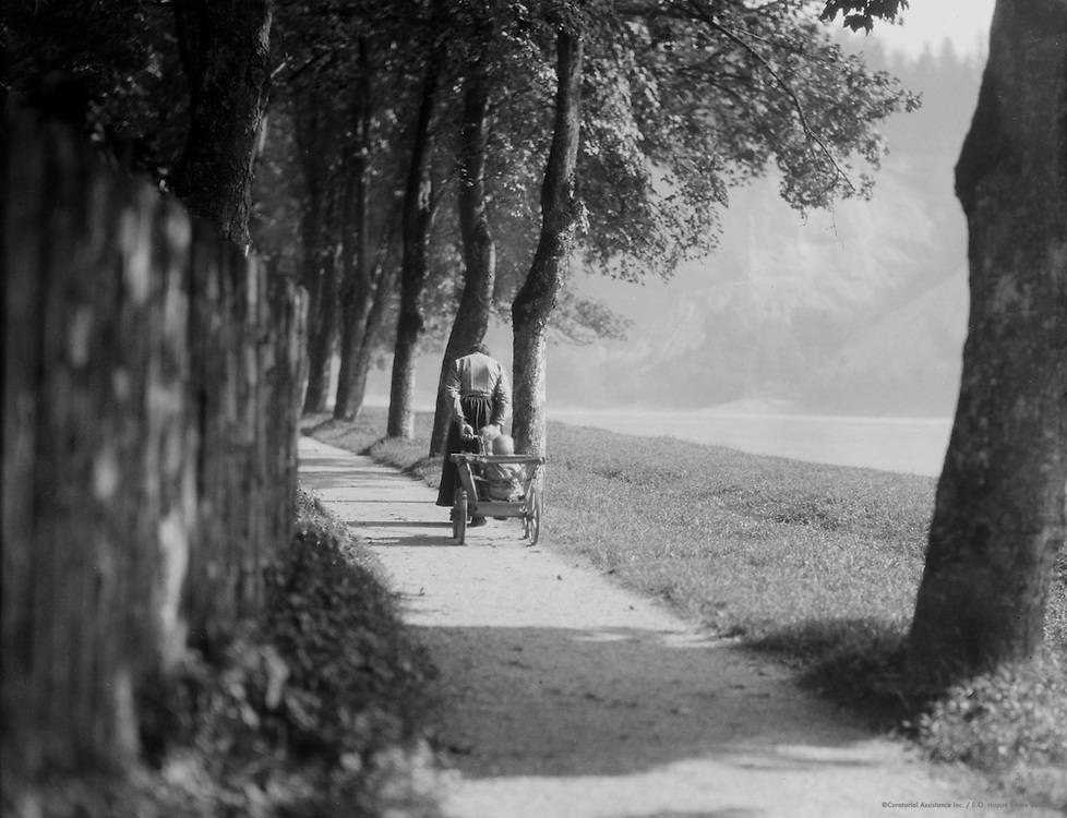 Woman pulling cart down path between trees, Germany, c1934