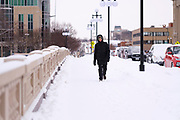 08 FEBRUARY 2021 - DES MOINES, IOWA: A bundled up pedestrian crosses the Court Ave Bridge over the Des Moines River in downtown Des Moines. Central Iowa, including Des Moines, is enduring its coldest winter in 25 years. Daily high temperatures this week are not expected to go above 10F (-12C) and nightly lows are expected to be about -5F (-20C). In addition to the cold weather, this is the second snowiest winter in Des Moines history. So far this winter there has been more than 44 inches (111 centimeters) of snow. Des Moines normally gets about 35 inches (90 centimeters) of snow all winter.         PHOTO BY JACK KURTZ