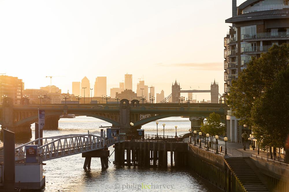 Sunrise over London cityscape including Southwark bridge, Cannon Street Railway Bridge and Tower bridge, London, England, UK