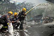 May 19 - BANGKOK, THAILAND: Thai firefighters try to put out a barricade fire in Lumpini Park during the Thai government crack down against Red Shirt and anti government protesters. The Royal Thai Army attacked anti-government protesters May 19 with troops and armored personnel carriers. Photo by Jack Kurtz
