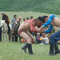 Nomadic herders wrestle at a naadam festival on a remote pass near Muren, Mongolia. This ancient sport is immensely popular across the country, and legend says that men wear their unique costumes to prove that they are not women, after an early empress humiliated her warriors by beating them.