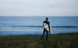 © Licensed to London News Pictures. <br /> 18/11/2014. <br /> <br /> Redcar, United Kingdom<br /> <br /> A surfer stands and looks out over the surf near Redcar in Cleveland.<br /> <br /> Photo credit : Ian Forsyth/LNP