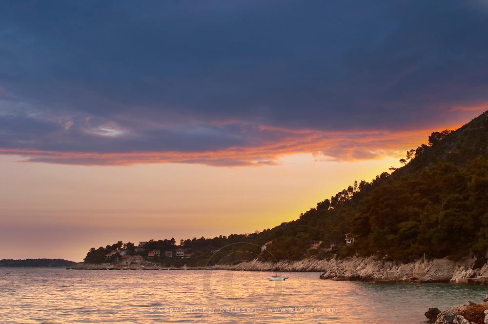 The Brna bay at sunset, bright orange sky, sky reflected in the sea water. Holiday homes on the hillside. Prizba village. Korcula Island. Prizba, Riva Apartments, Danny Franulovic. Korcula Island. Dalmatian Coast, Croatia, Europe.
