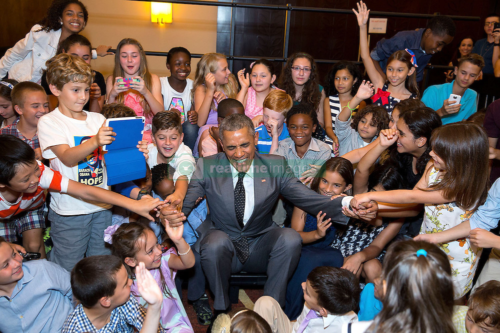 Children help President Barack Obama get up after a group photo during a U.S. Embassy meet and greet in Panama City, Panama, April 9, 2015. (Official White House Photo by Pete Souza)<br /> <br /> This official White House photograph is being made available only for publication by news organizations and/or for personal use printing by the subject(s) of the photograph. The photograph may not be manipulated in any way and may not be used in commercial or political materials, advertisements, emails, products, promotions that in any way suggests approval or endorsement of the President, the First Family, or the White House.