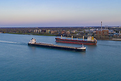 April 28, 2019 - Detroit, Michigan, U.S. - Detroit, Michigan - Great Lakes freighters on the Detroit River. The American Mariner (foreground) , a self-unloading bulk cargo carrier, steams downriver past Detroit and Windsor, Ontario on the Detroit River, while the bulk carrier Lyulin passes it going upriver. (Credit Image: © Jim West/ZUMA Wire)