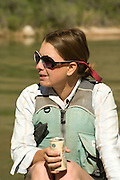 Olivai Markham (MR on file) enjoys a shot of Starbucks while riding a raft, Coloradao River, Grand Canyon National Park, Arizona, US