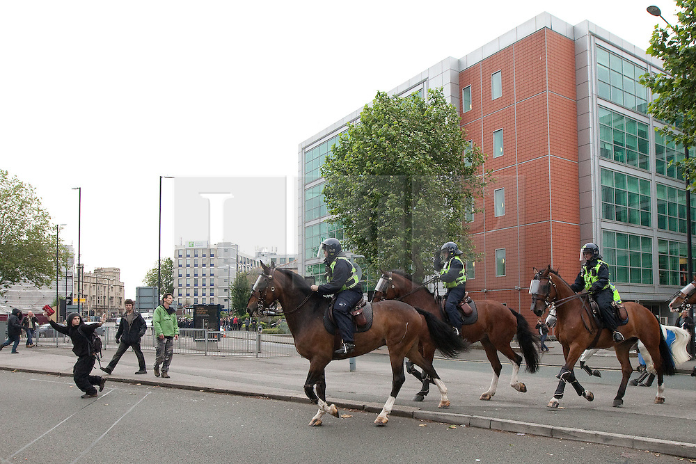 © Licensed to London News Pictures. 14/07/2012. Bristol , UK . Police use horses to break through anti fascists who are blocking the road. Anti fascist protesters clash with police as they attempt to block the route for EDL supporters to leave their demontration . The English Defence League hold a march and demonstration in Bristol . Photo credit : Joel Goodman/LNP