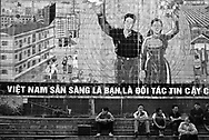 Vietnamese people sit on stairs and wait. A big communist propaganda built with tiles cover the background. Nam Phao-Cau Treo border control station between Laos and Vietnam, Asia