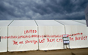 Greece . Idomeni. The now closed border crossing between Greece and Macedonia (Fyrom). Large UNHCR (United Nations High Commission for Refugees) dormitory tent wiith graffiti saying 'They are starving. Let them cross the border'.