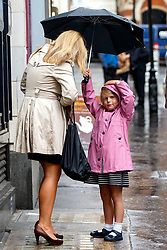 © Licensed to London News Pictures. 26/08/2015. London, UK. A girl sheltering her mother during heavy rain in central London on Wednesday, August 26, 2015. Photo credit: Tolga Akmen/LNP