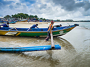 18 JULY 2016 - KUTA, BALI, INDONESIA:  A fishing crew pushes their outrigger canoe into the ocean to go fishing from Pasar Ikan pantai Kedonganan, a fishing pier and market in Kuta, Bali.   PHOTO BY JACK KURTZ