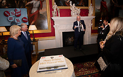The Prince of Wales and the Duchess of Cornwall listen to a speech by photographer Arthur Edwards during a tea party held at Spencer House in London to celebrate 70 inspirational people marking their 70th birthday this year.