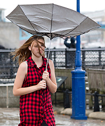© Licensed to London News Pictures. 10/08/2018. London, UK.  A woman loses control of her umbrella during a heavy rain shower and wet weather near the Tower of London at lunchtime today.  Photo credit: Vickie Flores/LNP