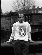 """Liam Brady Models World Cup Sweatshirt.  (T11)..1989..06.12.1989..12.06.1989..6th December 1989..To celebrate qualification for the World Cup at """"Italia 90"""" a range of clothing was produced for the many fans who would travel to Italy. Thousands of Irish fans are already making arrangements to follow the 'Boys In Green', on hopefully a journey to World Cup glory...Image shows Ireland midfielder, Liam Brady, modeling one of the shirts produced for fans supporting the Irish team in Italy."""