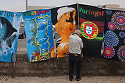 A man in a local Saturday market adjusts merchandise of sexist and Portugal-themed souvenir towels, on 19th July, in Estarreja, Portugal. A woman weaing a thong and a stetson-tyle cowboy hat shows a bare back and the others feature a map of the country with known seaside resorts and the national football emblem.