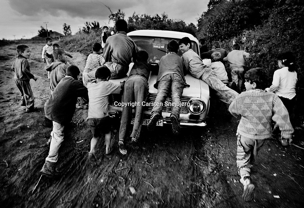 A visitor has been foolhardy enough to drive his Lada into the ghetto. The car is soon the draw among the excited children and when the driver tries to leave, backing up the dirt road, one kid steps on the licence plate in an attempt to mount the hood and it breaks off. All efforts from the driver to get the children off the car are futile and as the Lada reaches the highway the children start throwing rocks at it.