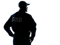 Rear view of a serious afro American policeman with hands on hip looking to his side on white isolated background