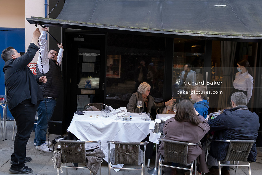 On the day that the UK government eased Covid restrictions to allow non-essential businesses such as shops, pubs, bars, gyms and hairdressers to re-open, bar staff adjust the awning outside their business on Frith Street in Soho, on 12th April 2021, in London, England.