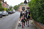 Morris dancers from Beorma Border Morris dancing troupe in Kings Heath walk along School Road after visiting a local friend on May Day under Coronavirus lockdown on 1st May 2020 in Birmingham, England, United Kingdom. These two women from the Beorma Morris are wearing their full costumes including rags and tatters, fishnet tights and feathers, and with distinctive blackened faces. Many morris sides through history blackened their faces, and Blacking up is reputed to have been as some form of disguise because the performers many of whom had jobs in agriculture, were begging, which was both illegal and could bring them shame. If so, the black face must have been a custom that saved face on the part of dancers and audience alike. The Coronavirus or Covid-19 is a new respiratory illness that has not previously been seen in humans. While much or Europe has been placed into lockdown, the UK government has put in place more stringent rules as part of their long term strategy, and in particular social distancing.