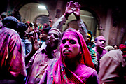 Holi festival, India, on wednesday, mar. 9, 2009. Inside the Banket Bihari temple in Vrindavan. From the stage powder is thromn over the audience. People har raising there arms in respect to Krishna