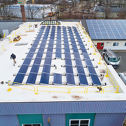 A PV Squared employee installing solar panels on the roof of a commercial building in Greenfield, Massachusetts.